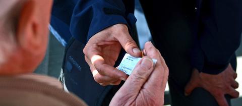 Ein Mann gibt einem anderen Mann in Uniform ein Ticket.