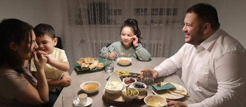 Fastenbrechen bei Familie Kilincarslan. Sie sitzen um einen Tisch, auf dem viele Schüsseln und Schalen mit Essen stehen.