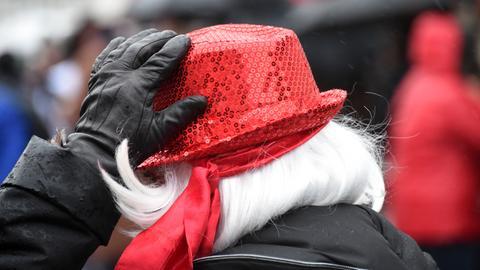 Eine Frau hält ihren Hut fest.