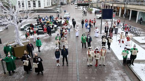 Miglieder von Fuldaer Fastnachtsvereinen stehen mit Einkaufstaschen auf dem Bahnhofsvorplatz