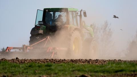 Staub wirbelt auf, während ein Bauer ein Feld bearbeitet.