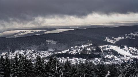 Dunkle Wolken ziehen über das winterliche Schmitten und den Feldberg.