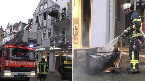 Bildkombo: Feuerwehrauto, Einsatzkräfte/ Feuerwehrmann spritzt auf Straße Sessel ab