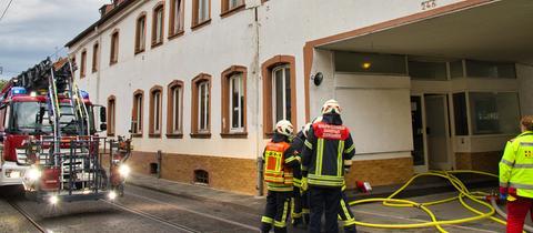 Feuerwehrleute stehen vor dem Haus, in dem es gebrannt hat.