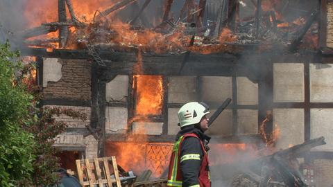 Ein Feuerwehrmann vor der brennenden Scheune in Bad Emstal