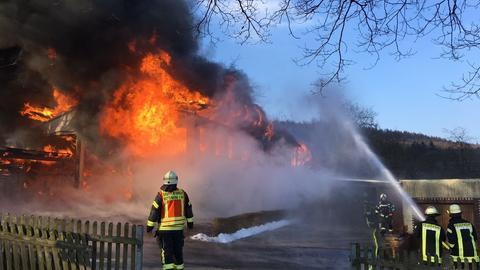 Feuerwehrmann vor brennender Lagerhalle in Frohnhausen