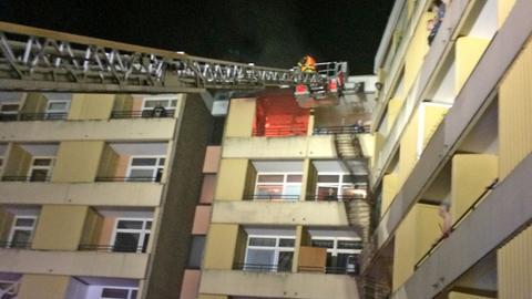 Von der Drehleiter aus löschen Feuerwehrmänner die brennende Wohnung im vierten Stock.