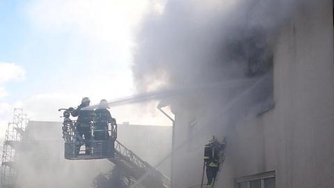 Feuerwehrmänner löschen von außen eine brennende Wohnung.