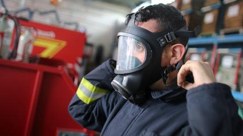 Feuerwehrmann zieht Atemschutzmaske auf