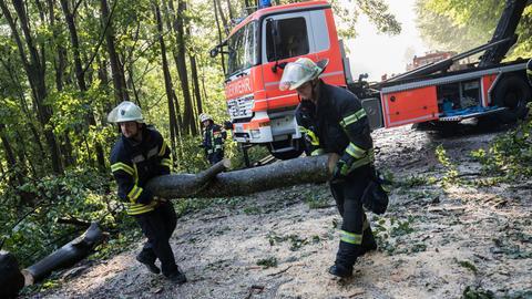Feuerwehrleute tragen in Wiesbaden auf einer Verbindungsstraße in Richtung Schlangenbad einen Teil eines eines zuvor zersägten Baumes zur Seite, der die Fahrbahn versperrt hatte.