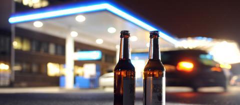 Zwei Bierflaschen vor einer nächtlichen Tankstelle