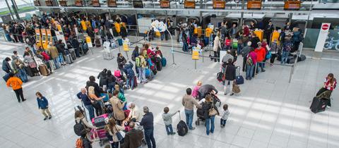 Passagiere warten am Abflugschalter