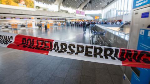 """Flatterband mit der Aufschrift """"Polizeiabsperrung"""" vor der Schalterhalle im Frankfurter Flughafen."""