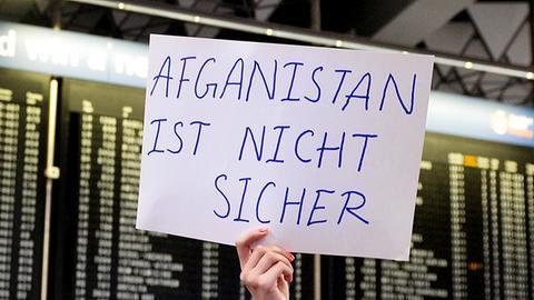"""Ein Pappschild vor der Abflugtafel, auf dem in Großbuchstaben steht: """"Afganistan (sic!) ist nicht sicher"""""""