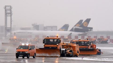 Schneepflüge fahren über das Vorfeld des Frankfurter Flughafens.