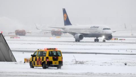 Räumfahrzeuge auf dem Vorfeld des Flughafens Frankfurt hinter einem Lufthansa-Airbus.