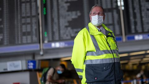 Ein älterer Mann in gelber Jacke steht am Flughafen vor der Anzeigetafel