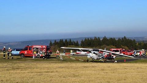 Das Unglücksflugzeug vom Typ Cessna  am Ende einer Landebahn, Einsatzkräfte