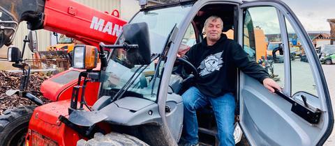 Fluthelfer Wilhelm Hartmann sitzt im Führerhaus eines Räumfahrzeuges und schaut in die Kamera.