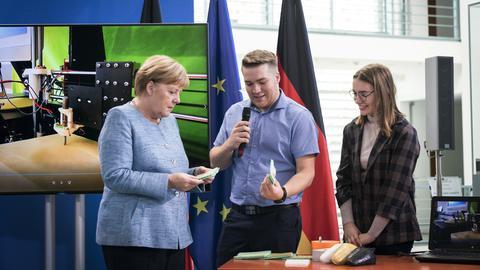 Die beiden Forscher Adrian (Mitte) und Anna Fleck (rechts) präsentieren Bundeskanzlerin Angela Merkel (CDU) 2018 ihre Erfindung.