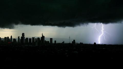 Ein Blitz erhellt den dunklen bewölkten Himmel über der Frankfurter Skyline