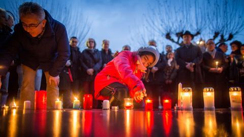 Der SPD-Landtagsabgeordnete Turgut Yüksel und ein Mädchen entzünden am Mittwoch Kerzen auf dem Frankfurter Paulsplatz.