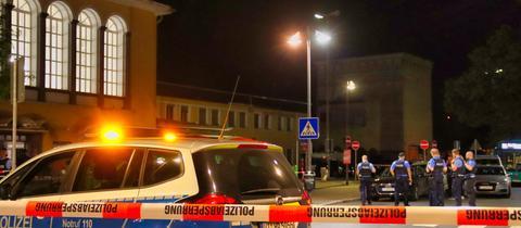 Vor einem Bahnhosgebäude steht ein Polizeiauto sowie mehrere Einsatzkräfte. Der Bereiche ist mit Flatterband abgesperrt.