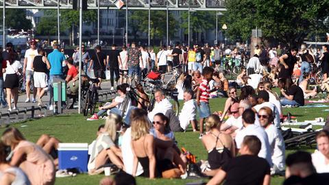 Sonnenhungrige in großer Zahl genießen den Himmelfahrtstag nach den Lockerungsmaßnahmen in der Coronavirus-Krise die warmen Temperaturen und die Sonnenstrahlen auf einer Liegewiese und der Uferpromenade am Mainufer in der Innenstadt Frankfurt und halten nicht immer den Mindestabstand ein