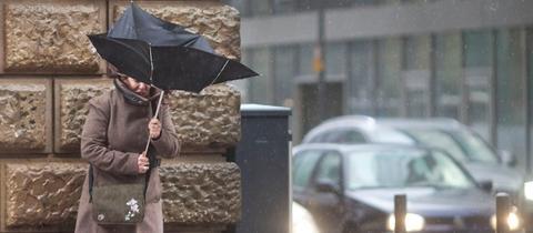 Kampf mit dem Regenschirm bei Wind in Frankfurt.