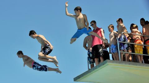 Jugendliche springen vom Turm des Mühltalbads in Darmstadt-Eberstadt
