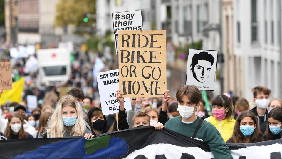 """Ein Demonstrationszug, in dem ein junger Mann ein Plakat mit der Aufschrift """"Ride bike or go home"""" hält, ist am globalen Streiktag für Soziale- und Klimagerechtigkeit von Fridays for Future am Mainkai unterwegs zu einer Abschlusskundgebung auf einer Mainbrücke."""