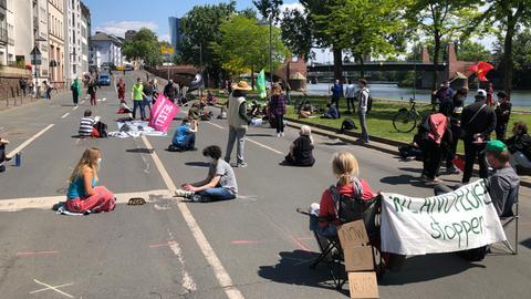 Klimaaktivisten von Fridays for Future demonstrieren in Frankfurt auf einer Straße am Mainufer