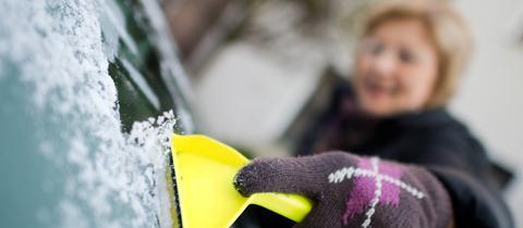 Eine Frau kratzt mit einem Eiskratzer eine vereiste Frontscheibe eines Autos frei