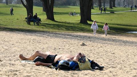 Mann liegt am Strand und sonnt sich.