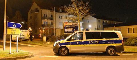 Die Polizeifahrzeug steht vor Mehrfamilienhaus