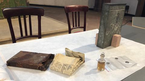 Auf einem Tisch liegen verschiedene Gegenstände aus der Zeitkapsel.