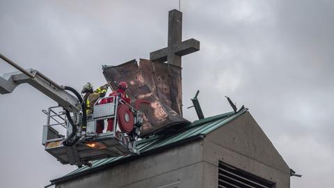 Von einem Hubsteiger aus versuchen Feuerwehrmänner, das Blechdach eines Kirchturms im Frankfurter Sadtteil Gallus zu sichern, das sich durch das Orkantief losgerissen hatte.