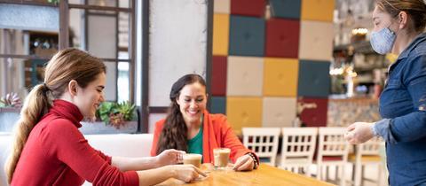Zwei Frauen sitzen in einem Café und werden von einer Kellnerin mit Maske bedient