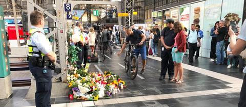 Ein Fahrradfahrer legt an Gleis 7 des Frankfurter Hauptbahnhofs Blumen für den getöteten Achtjährigen ab.