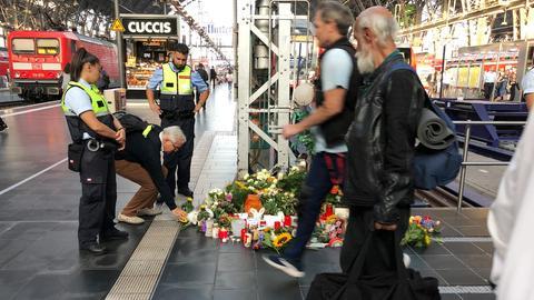Ein Passant legt an Gleis 7 des Frankfurter Hauptbahnhofs Blumen für den getöteten 8-Jährigen ab