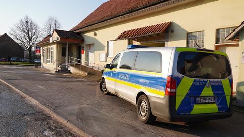 Polizeiauto und Absperrband vor Bank.