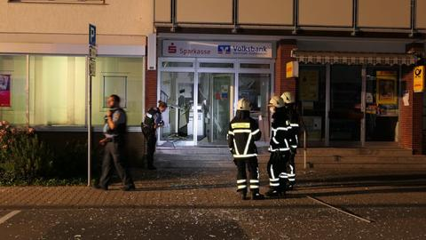 Einsatzkräfte von Polizei und Feuerwehr stehen einer Bankfiliale in Pfungstadt.