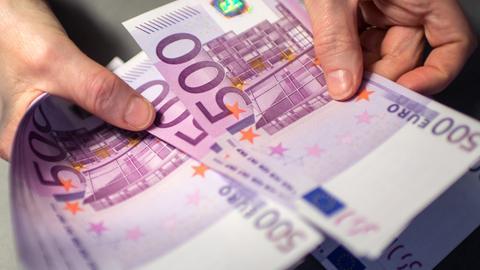 Eine Hand hält ein Bündel 500-Euro-Scheine.