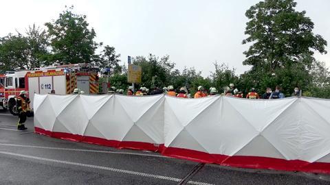 Einsatzkräfte stehen auf einer Straße hinter einer langen Sichtschutzwand.