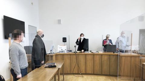 Gerichtssaal mit einem Angeklagten und Gerichtsmitarbeitern.