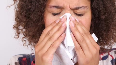 Frau hält sich mit beiden Händen ein Taschentuch vor die Nase
