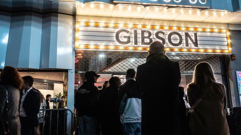 """Mehrere Menschen stehen in einer Warteschlange vor einem Eingangstor, darüber steht in leuchtender Schrift der Name """"Gibson""""."""