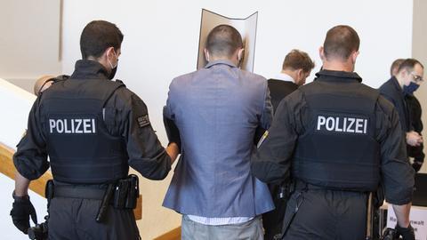 Polizisten führen einen Angeklagten zu seinem Platz in der Gießener Kongresshalle.