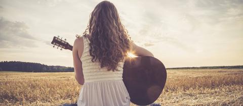 Junge Frau sitzt auf Feld und spielt Gitarre