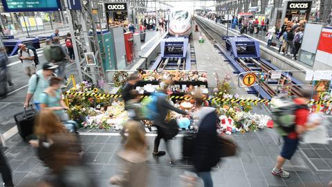 Passanten gehen am Gleis 7 des Hauptbahnhofs an einer Gedenkstelle für den getöteten Jungen vorbei.